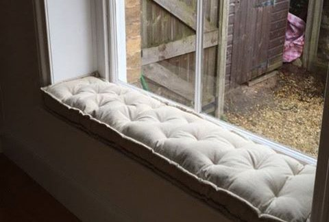 Tufted window seat cushion with piped edges